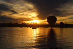 Hot Air Balloon Lake Sunset. A Hot Air Balloon touching down on a lake in front of a bright sunset  in silhouette Royalty Free Stock Images