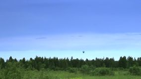 Hot air balloon landing in blue sky time-lapse. Stock footage stock video footage
