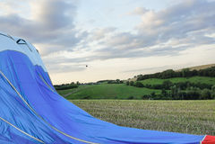 A hot air balloon landing in a field Stock Photos