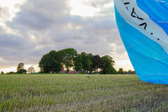 Hot air balloon landing in a green field Stock Images