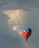 Hot Air Balloon Lit Through the Clouds Stock Photo