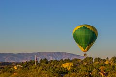 Hot Air Balloon At Low Altitude. Green & Yellow Hot Air Balloon Flying At Low Altitude In Early Morning royalty free stock images