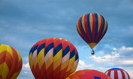 Hot Air Balloon moving away from the field Royalty Free Stock Images