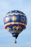 Hot air balloon moving up in blue sky. Stock Photography