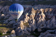 A hot air balloon navigates it way down the spectacular Rose Valley at sunrise, near Goreme in the Cappadocia region of Turkey. Royalty Free Stock Images