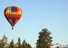 Hot Air Balloon over Bend,OR. Colorful hot air balloon floating in the sky with the Oregon cascade mountains in the back ground Stock Photos