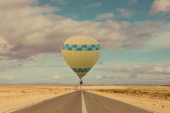 Hot air balloon over desert and road stock images