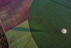 Hot air balloon over field Stock Images