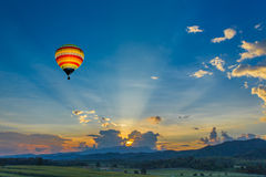 Hot air balloon over the fields at sunset Stock Photography