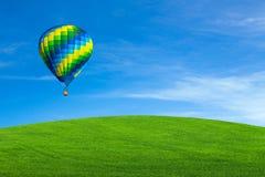 Hot air balloon over green field Stock Photo