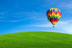 Hot air balloon over green field Royalty Free Stock Image