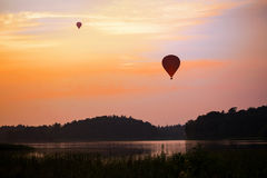 Hot air balloon over a lake and forest landscape in the evening Royalty Free Stock Images