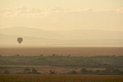 Hot air balloon over Masai Mara. Hot air balloon over the Masai Mara National Reserve at sunrise, Kenya, Africa Royalty Free Stock Photo