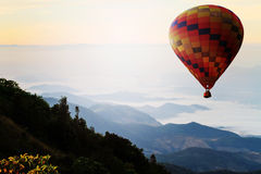 Hot air balloon over mountain in sunrise. Travel concept. Stock Images