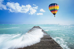 Hot air balloon over the ocean with pathway. Colorful Hot air balloon over the ocean with pathway Stock Image
