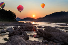 Hot air balloon over river and mountain Stock Photo