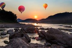 Hot air balloon over river and mountain Stock Photo