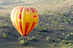 A hot air balloon over small hill Royalty Free Stock Photography