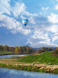 Hot air balloon Over  small river Royalty Free Stock Images