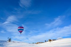 Hot-air Balloon Over Snow Covered Landscape And Small Rural Village, Bavaria, Germany Royalty Free Stock Images