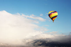 Hot Air Balloon Over Snowy Mountain. Hot air balloon over a snowy New Mexico mountain in a patch of blue sky Stock Photo