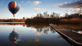 Hot air balloon over sunset lake with jetty Royalty Free Stock Image