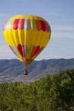 Hot Air Balloon Over Treed Hill. Yellow hot air balloon with heart shaped pattern rising from behind treed hill with foothills and residences visible in far Stock Images