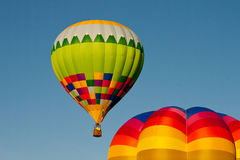 Hot air balloon passes over another Stock Image