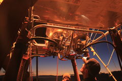 Hot Air Balloon Pilot checks flame burner. Burner throwing hot air and high flame for inflating hot air balloon for take off in early morning in Queensland Stock Photo