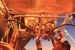 Hot Air Balloon Pilot checks flame burner. Burner throwing hot air and high flame for inflating hot air balloon for take off in early morning in Queensland Stock Image