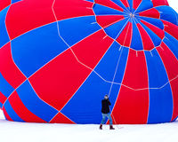 Hot Air Balloon Prep. A worker steadying a hot air balloon as it inflates at the Hudson Hot Air Affair in Hudson Wisconsin Royalty Free Stock Image