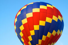 Hot air balloon of primary colors. A red, blue, and yellow hot air balloon showing just the top against blue sky Stock Image