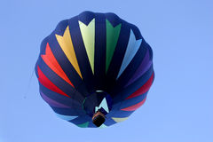 Hot air balloon in rainbow colors. From below, against a blue sky. passenger pointing to the distance. wild west balloon fest, cody, wyoming stock photography