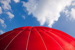 Hot air balloon - red. Top of bright red hot air balloon against a blue sky with clouds stock photo