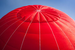 Hot air balloon - red. Red canopy of hot air balloon being inflated against a bright blue sky royalty free stock photography
