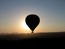 Hot air balloon ride sunrise. The sun rising behind a hot air balloon Royalty Free Stock Images