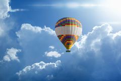 Hot air balloon rises very high in blue sky above white clouds Royalty Free Stock Image
