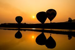 Hot air balloon in senset. Silhouette and reflection of hot air balloon going up in the sky when sunset Royalty Free Stock Photos