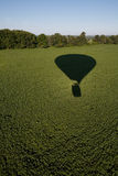 Hot air balloon shadow on field. Hot air balloon shadow on field with forest in background Stock Photo