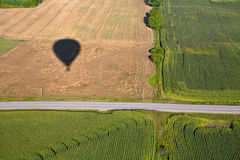 Hot air balloon shadow on field with road. Hot air balloon casting a shadow on a farmers field beside a country road Royalty Free Stock Photo