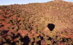 Hot Desert Shadow. Hot Air Balloon Shadow floating over brush and desert stock photo