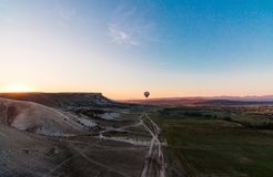 Hot air balloon shadow on the ground during sunrise flying over the valley and mountains royalty free stock photo
