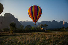 Hot air balloon on sky in Laos, Vang Vieng. Hot air balloon on sky landing on ground Royalty Free Stock Image
