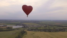Hot air balloon in the sky over a wheat field.Aerial view stock video footage