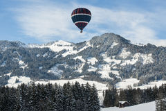 Hot air balloon over snowy alps. Hot-air-ballon over the pre alpin mountains in Germany Royalty Free Stock Photography