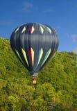 Hot Air Balloon Soaring High. Hot air Balloon in flight near trees on a semi cloudy day Royalty Free Stock Photos