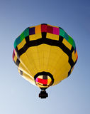 Hot air balloon soaring into the sky. Yellow hot air balloon soaring skyward towards the sun royalty free stock photography