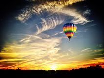 Hot Air Balloon. A hot air balloon soars through the evening sky royalty free stock images