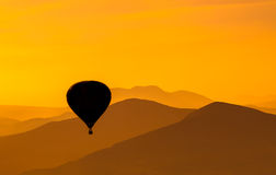 Hot Air Balloon at Sunrise. Hot air balloon flying at sunrise over mountains Stock Images