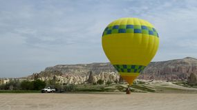 Hot Air Balloon Waiting For Take-Off in Cappadocia. Inflating a yellow hot air balloon in Cappadocia, Central Anatolia, Turkey Royalty Free Stock Photography